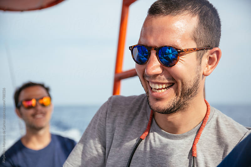 Close up of a young man's face laughing during a boat trip in the sea by Alejandro Moreno de Carlos for Stocksy United