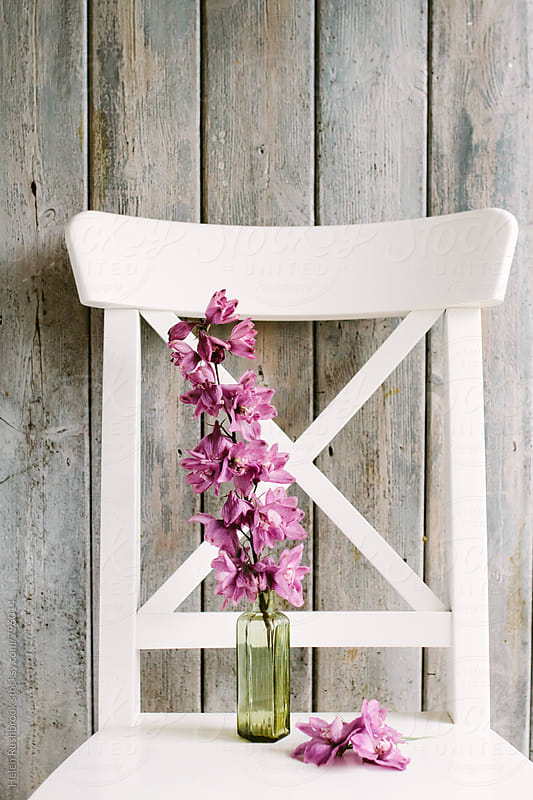 Delphinium flowers in an antique green bottle on a white chair. by Helen Rushbrook for Stocksy United