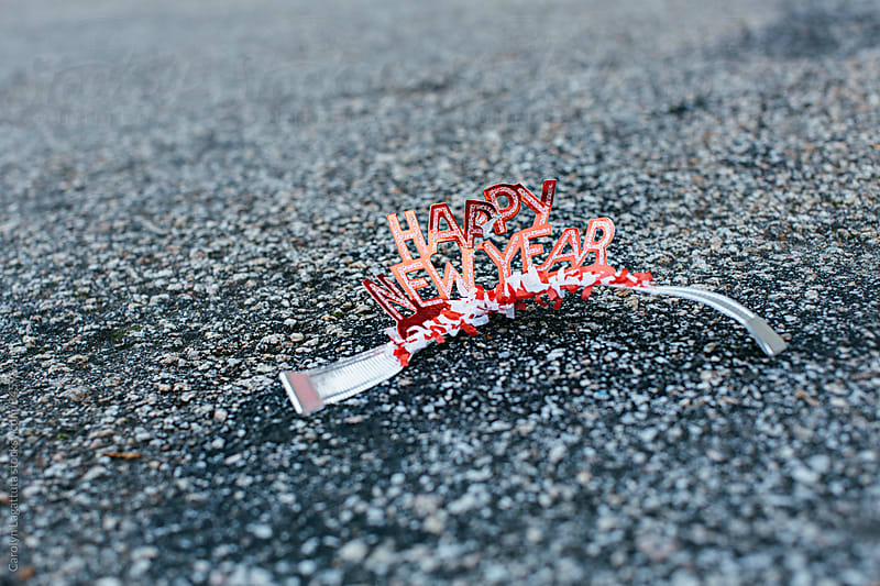Crumpled Happy New Year headband on the ground - after the party by Carolyn Lagattuta for Stocksy United