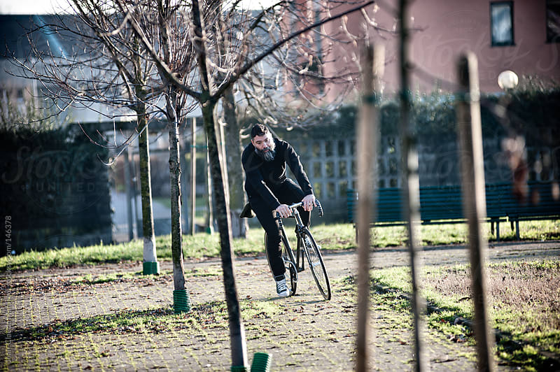 Hipster man ride his fixed gear bike in a park in a suburb of Milano by Jean-Claude Manfredi for Stocksy United