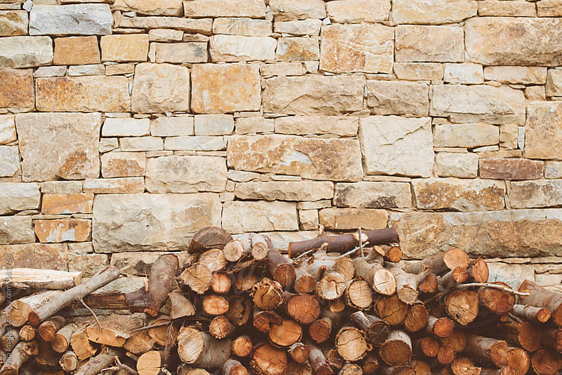 Pile of wood against stone wall by Aila Images for Stocksy United