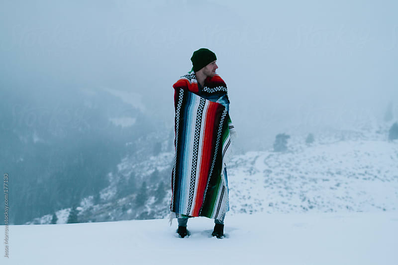 Young man with tribal blanket on a winter mountain by Jesse Morrow for Stocksy United