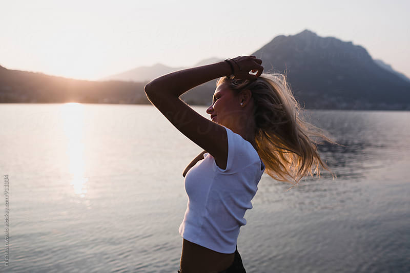Happy beautiful woman enjoying the sunset at the lake by michela ravasio for Stocksy United