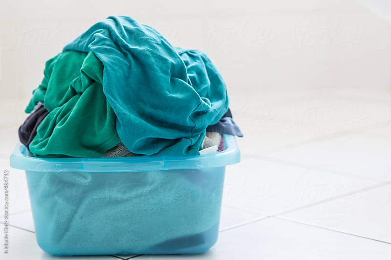 Laundry basket on a bathroom floor by Melanie Kintz for Stocksy United