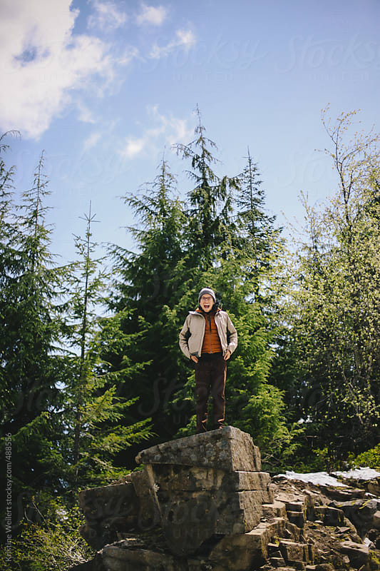 Smiling man standing on rock in the forest by Kristine Weilert for Stocksy United