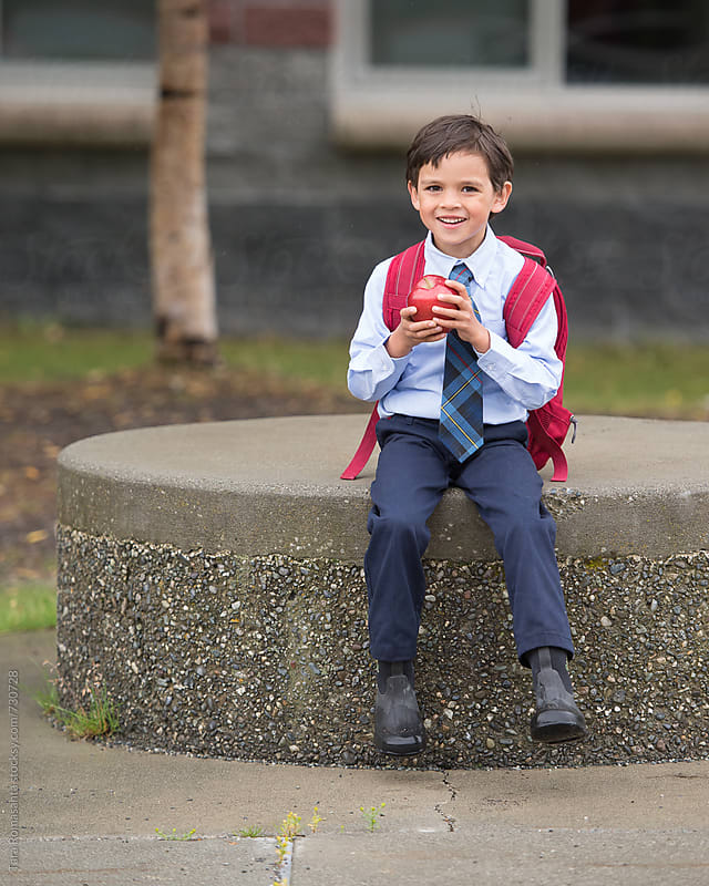 smiling boy on the first day back to school by Tara Romasanta for Stocksy United