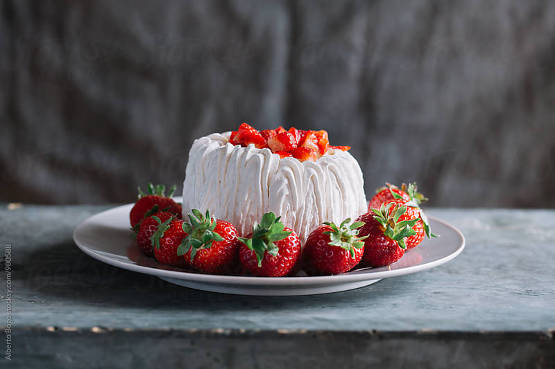 Delicious pavlova cake with strawberries by Alberto Bogo for Stocksy United