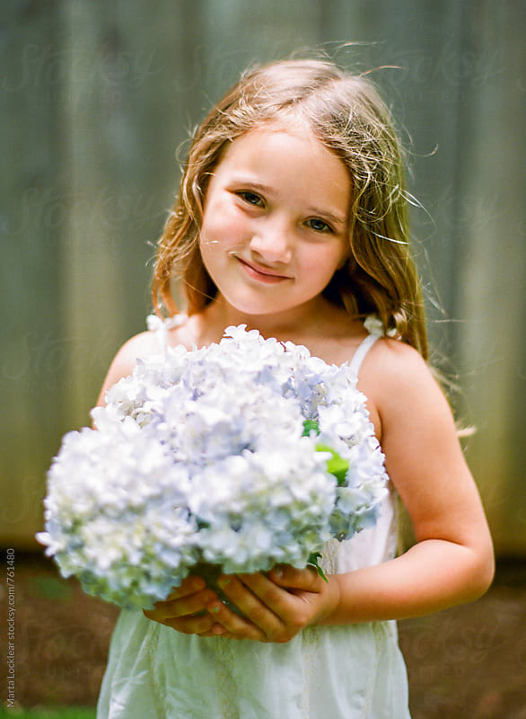 Girl holding hydrangea flowers by Marta Locklear for Stocksy United