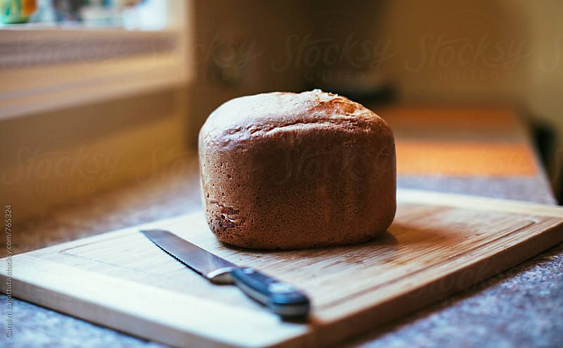 A  loaf of fresh baked, homemade bread with a knife on a cutting board by Carolyn Lagattuta for Stocksy United