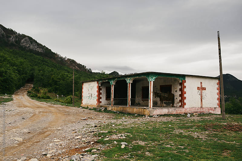 Ruin next to a unpaved road on a pass in Albania by Freek Zonderland for Stocksy United