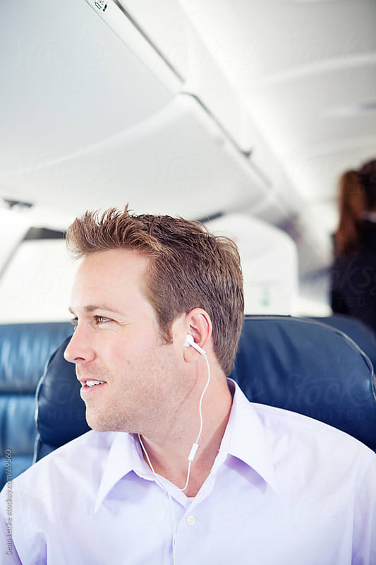Airplane: Man Listens to Headphones in First Class by Sean Locke for Stocksy United