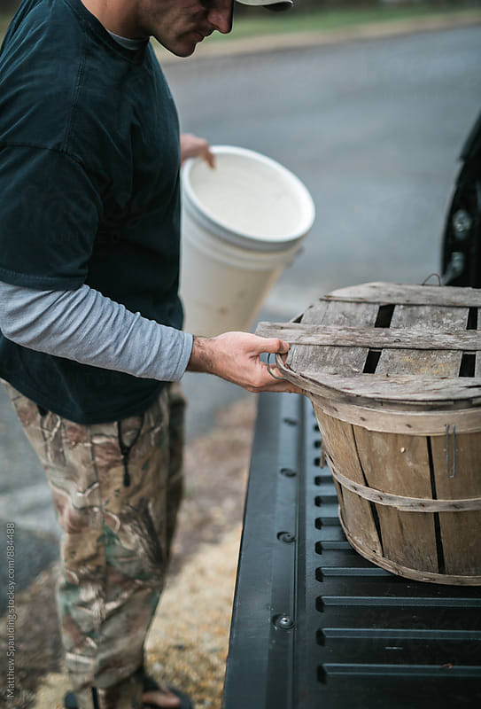 Man organizing storage baskets for fishing trip by Matthew Spaulding for Stocksy United