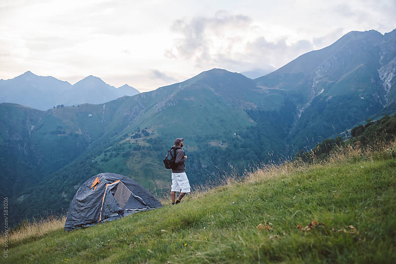 Man camping with a tent in mountain by GIC for Stocksy United