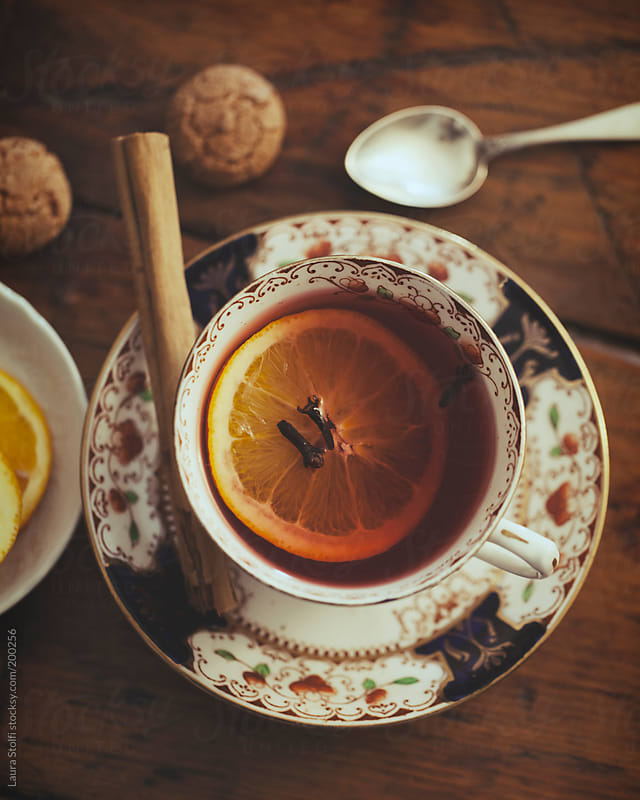 Wintry red fruits tea with cinnamon sticks, orange slice and cookies by Laura Stolfi for Stocksy United