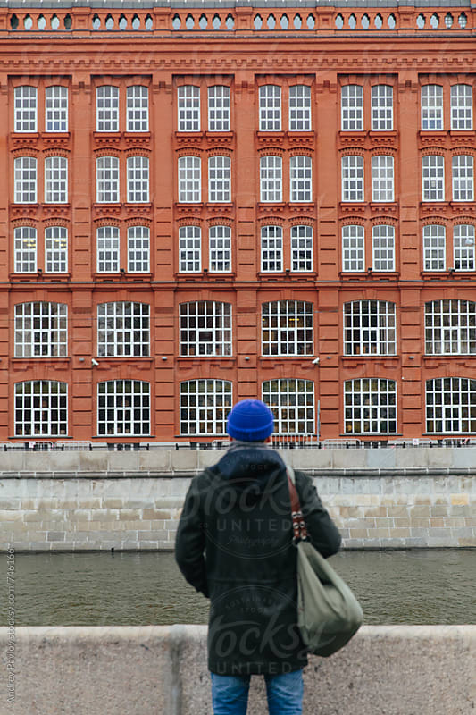 Man looking at the building from another side of river by Andrey Pavlov for Stocksy United