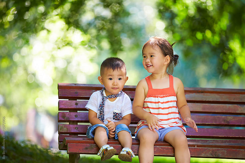 two happy little kids together outdoor sitting on the bench at park by Bo Bo for Stocksy United