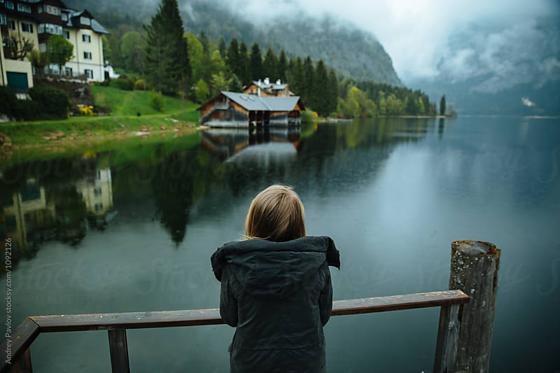 Back view of blonde traveler watching still lake in mountain village by Andrey Pavlov for Stocksy United