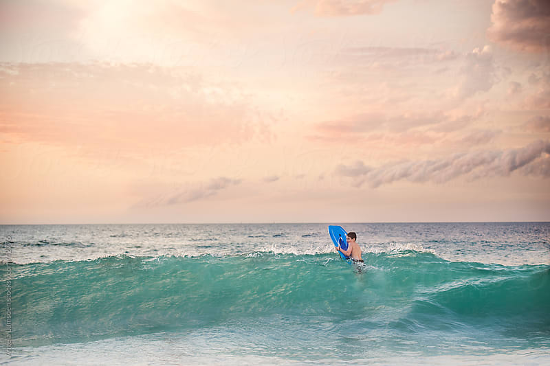 Young boy in a large wave in the ocean at sunset by Angela Lumsden for Stocksy United