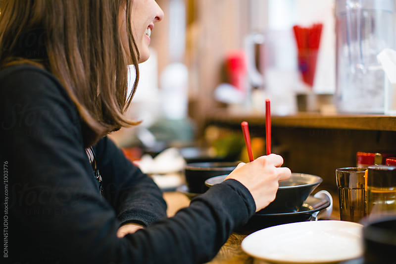 Closeup of a woman eating in a Japanese restaurant.  by BONNINSTUDIO for Stocksy United
