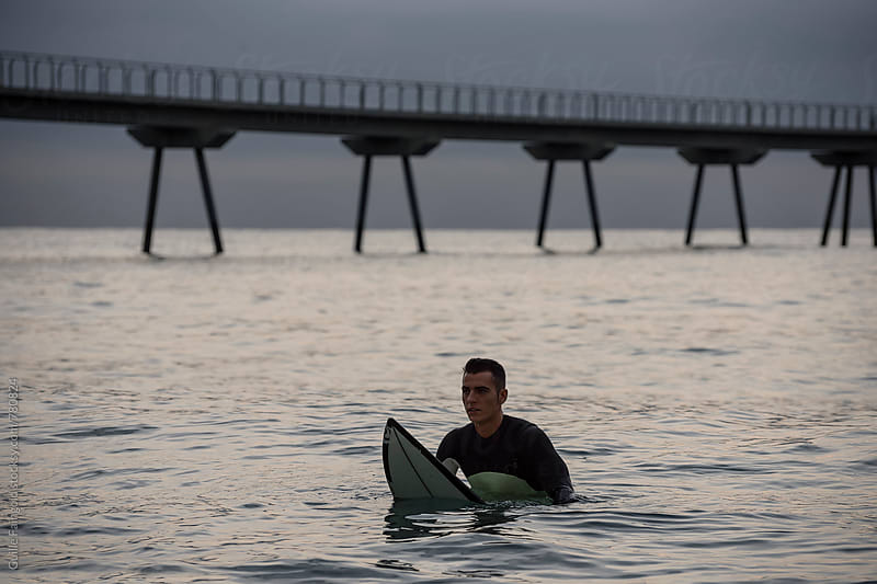 Surfer sits waiting on his surfboard for a wave by Guille Faingold for Stocksy United