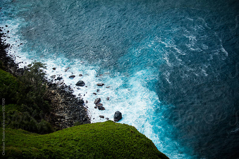 Overhead view of blue waves crashing on a rocky beach by Christian Tisdale for Stocksy United