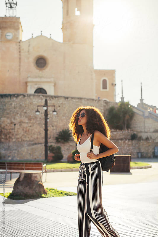 Chic female tourist visiting a beautiful village on sunny day. by BONNINSTUDIO for Stocksy United