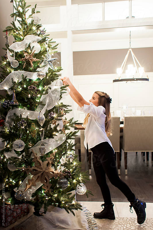 Little Girl Reaching to Hang Christmas Ornaments on Christmas Tree by JP Danko for Stocksy United