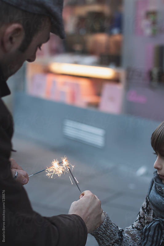 Father lighting up sparkler to his son by Beatrix Boros for Stocksy United