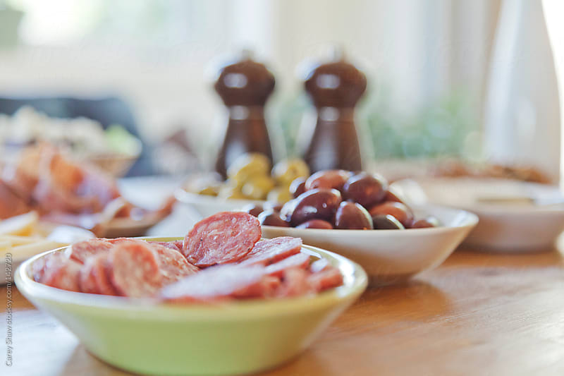 Table setting with meat, olives and cheese by Carey Shaw for Stocksy United