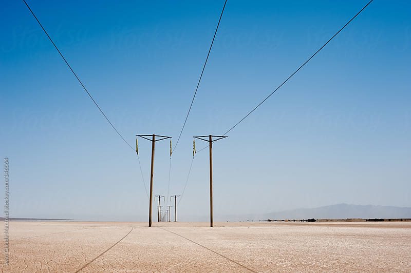 Pylons Electric power line  in the desert. by Jean-Claude Manfredi for Stocksy United