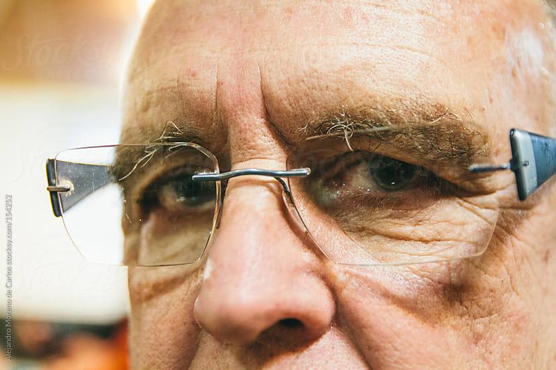 Senior man eyes close up wearing glasses by Alejandro Moreno de Carlos for Stocksy United