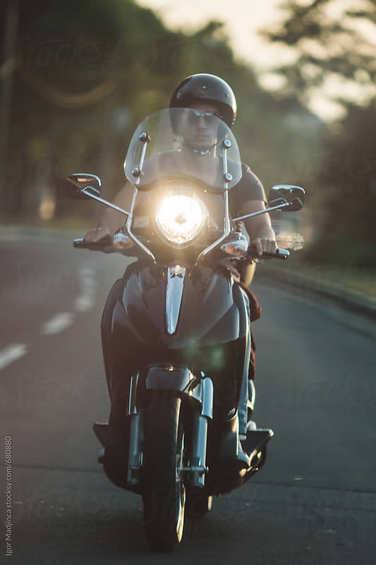 on the road, biker and sunset by Igor Madjinca for Stocksy United