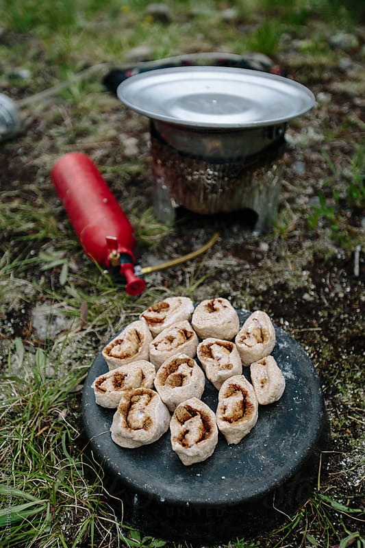 Backcountry cinnamon rolls prepared with camp stove by Matthew Spaulding for Stocksy United