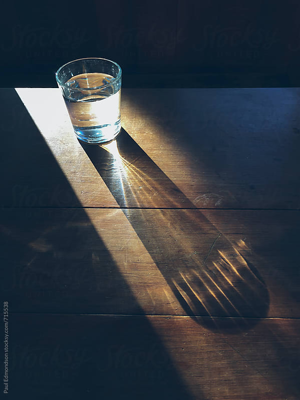 Sunlight shining through glass of water on wood table by Paul Edmondson for Stocksy United