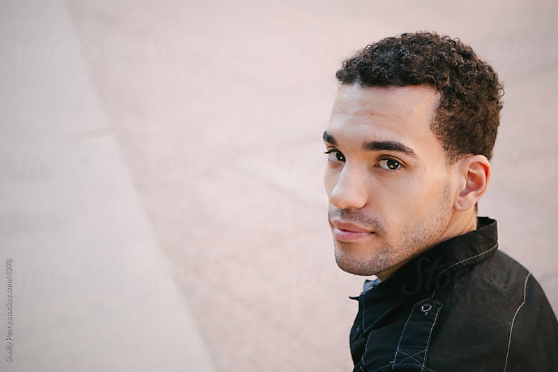 Young man looks at the camera over his shoulder. by Shelly Perry for Stocksy United