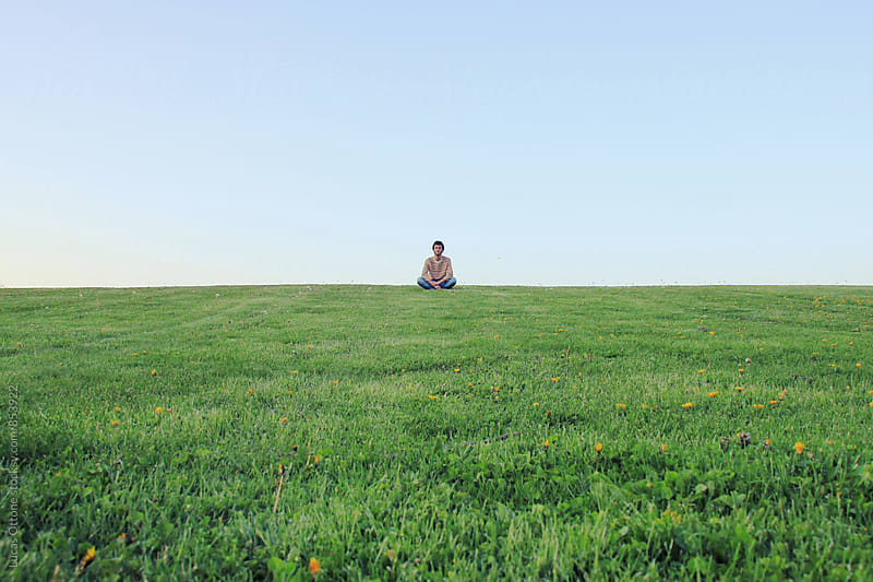 Lonely man sitting at the top of a grass hill by Lucas Ottone for Stocksy United