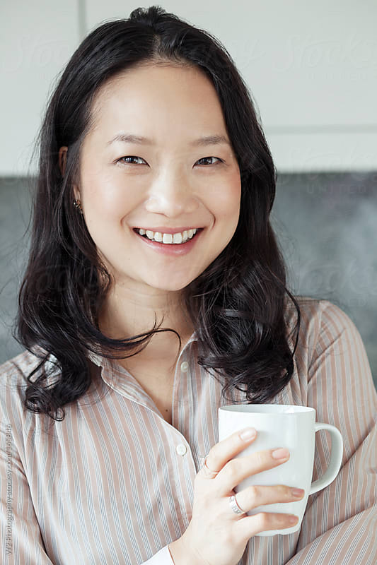 Happy beautiful woman taking a break with a cup of coffee by W2 Photography for Stocksy United