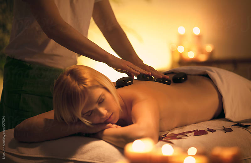 Woman enjoying spa treatment with hot stones. by Mosuno for Stocksy United