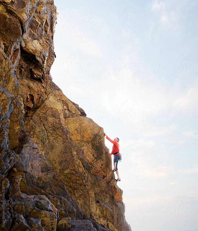Senior male rock climber, climbing steep rock face, with seascape in the background. by Hugh Sitton for Stocksy United
