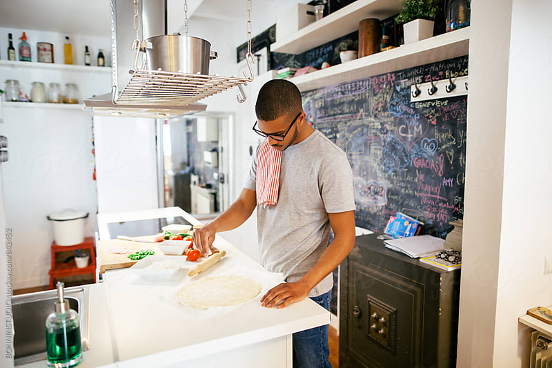 Man preparing a pizza dough in the kitchen. by BONNINSTUDIO for Stocksy United