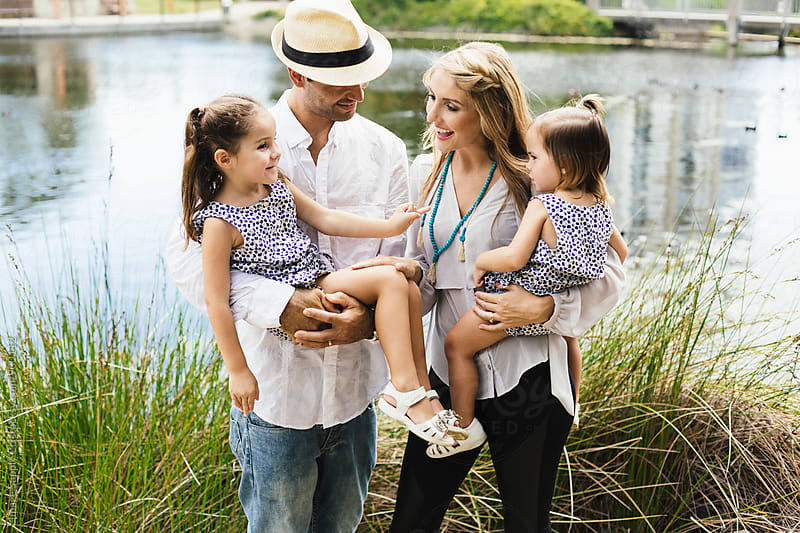 Young family standing by lake happily with their two young daughters. by Image Supply Co for Stocksy United