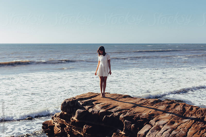 Young woman standing on the edge of a large rock over the ocean by paff for Stocksy United