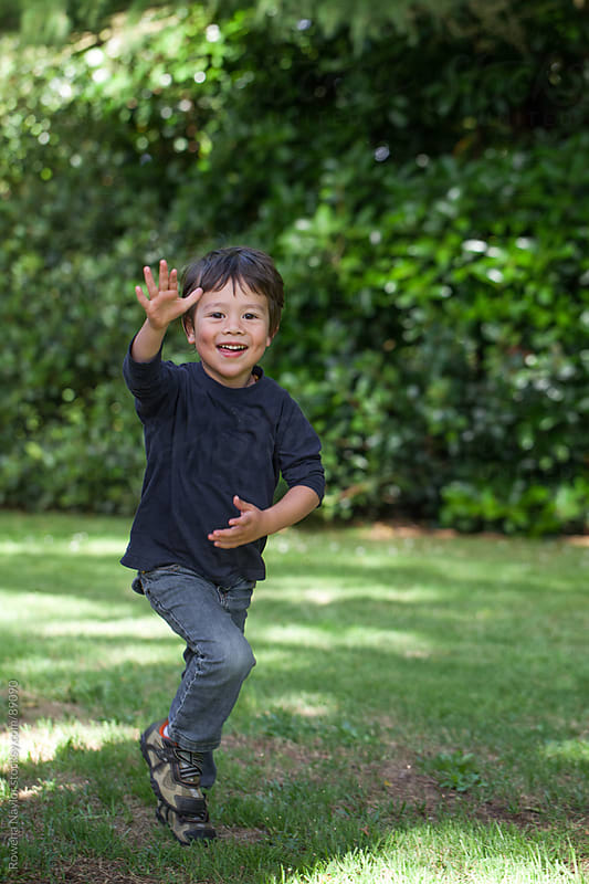 Toddler playing outdoors and running towards camera waving by Rowena Naylor for Stocksy United