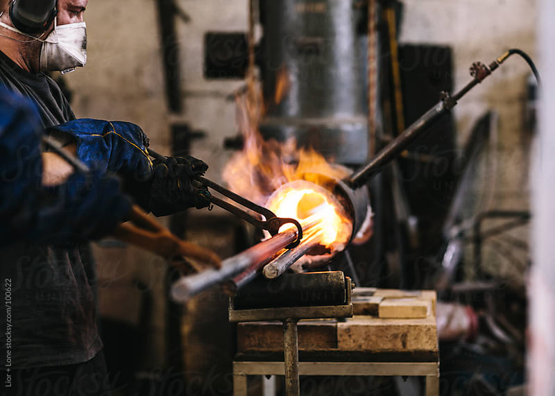 Man working steel poles in gas forge by Lior + Lone for Stocksy United