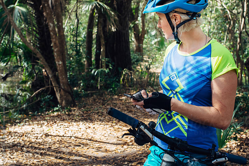 Female mountain bike cyclist checking her mobile device by Gabriel (Gabi) Bucataru for Stocksy United