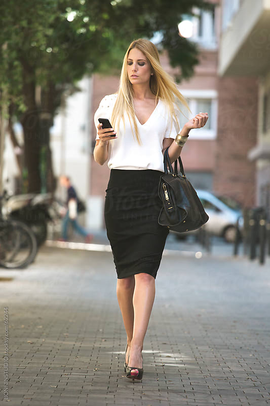Young businesswoman with smartphone and big bag in the city. by BONNINSTUDIO for Stocksy United