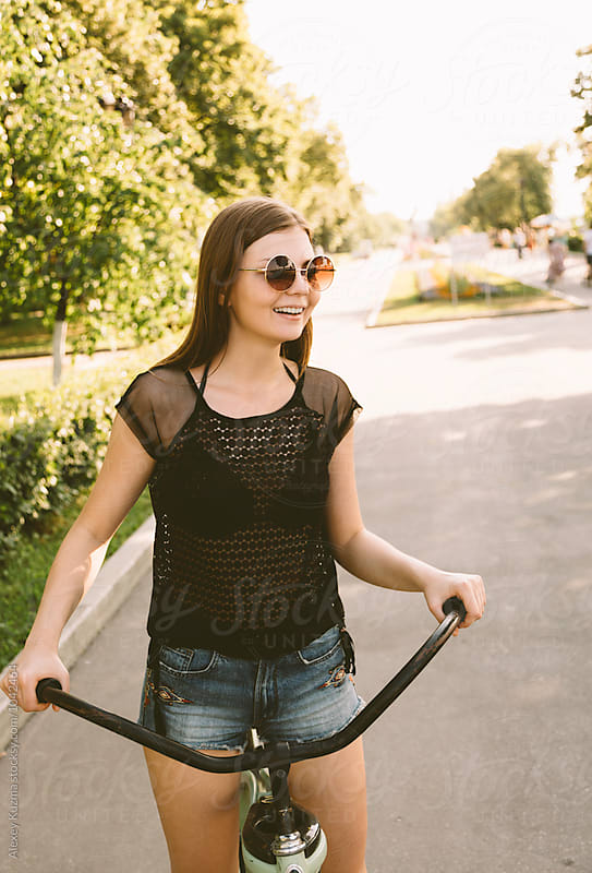 Happy Young Woman Riding a Bike in the Park by Alexey Kuzma for Stocksy United