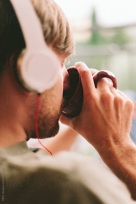 Young Man with Headphones Drinking by HEX. for Stocksy United