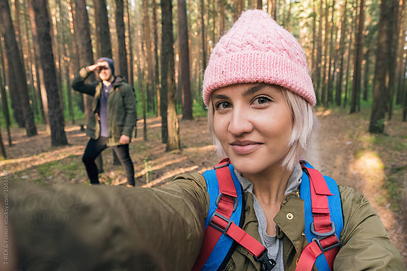 Adventurous backpacker in pink hat taking selfie in forest by Danil Nevsky for Stocksy United