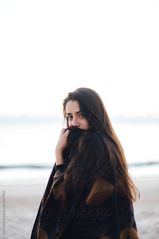 A girl on a beach wearing a blanket by Jake Elko for Stocksy United